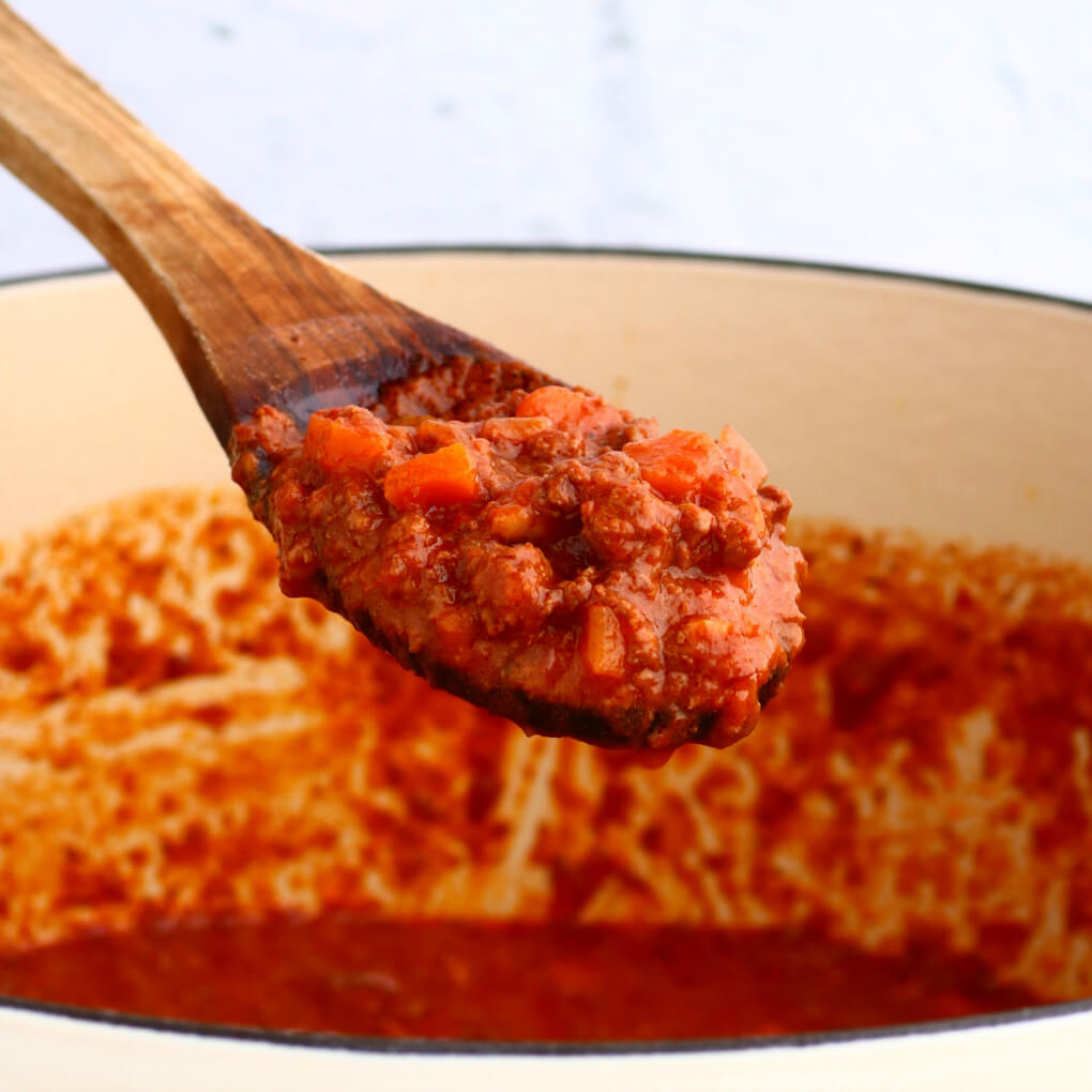 A wooden spoon holds bright red rich meat sauce over a pot of sauce.