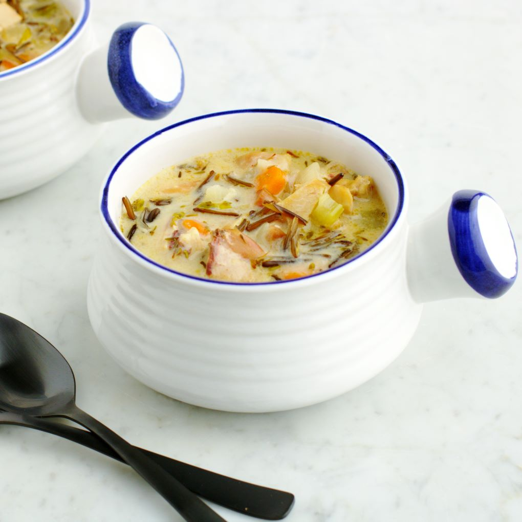 A white bowl filled with creamy chicken wild rice soup.