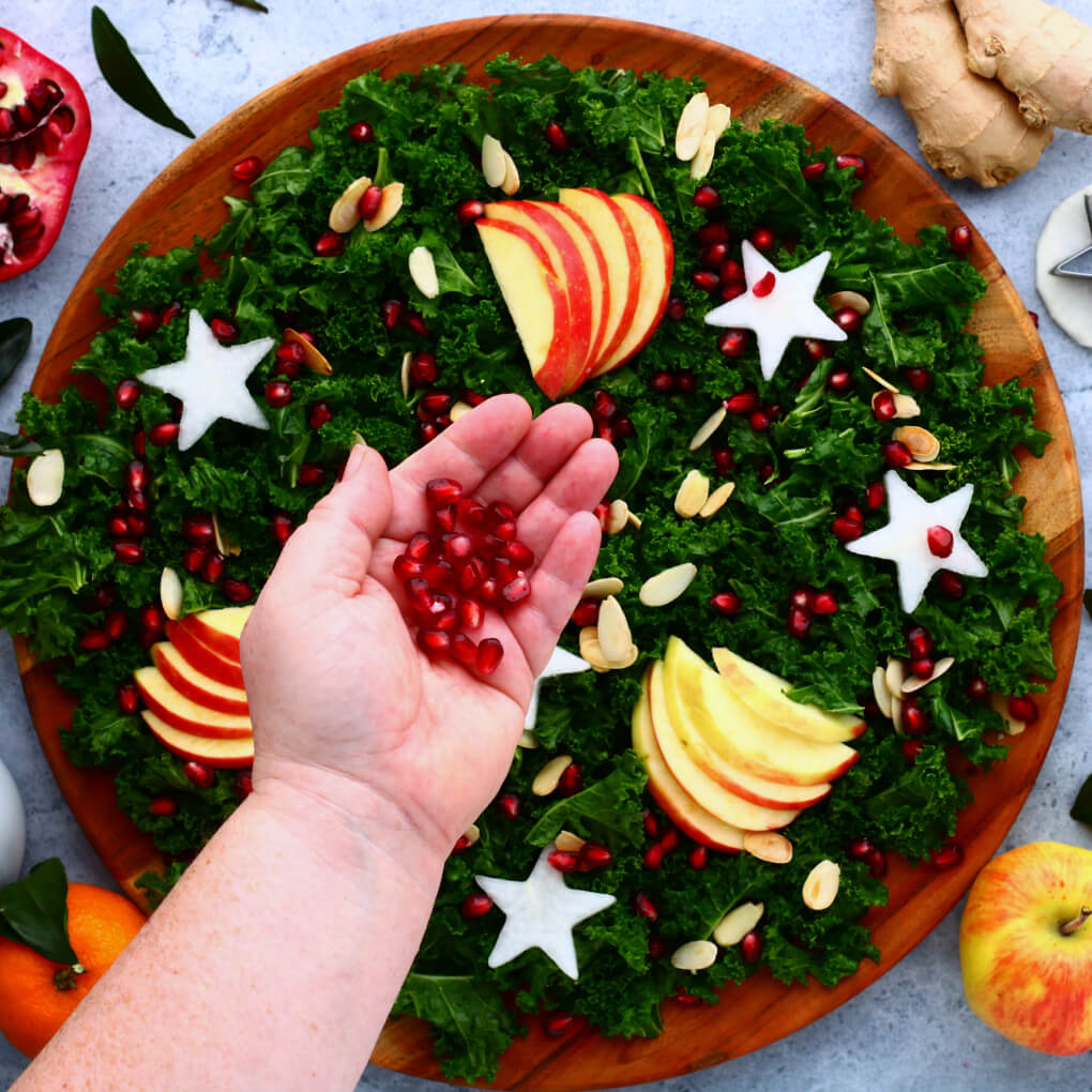 A hand holds red pomegranate seeds over a leafy green massaged kale salad topped with apple slices, daikon stars, and almonds.