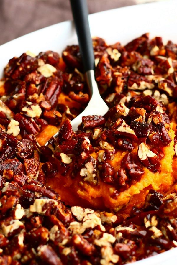 A serving spoon lays inside a white casserole dish of Sweet Potato Crunch mashed sweet potatoes topped with chopped pecans.