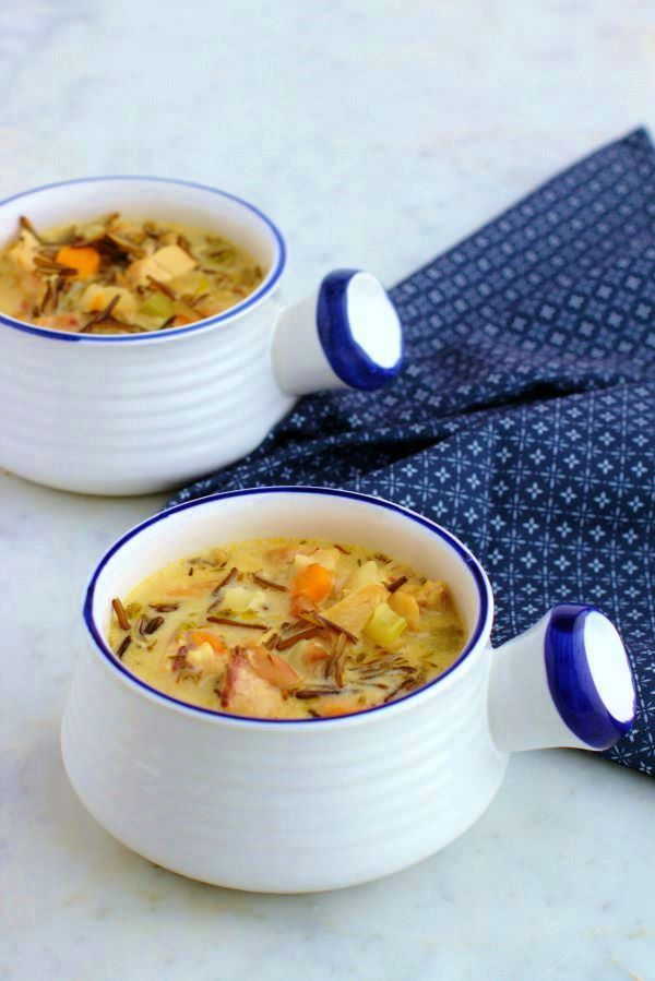 Two white bowls filled with creamy chicken wild rice soup.