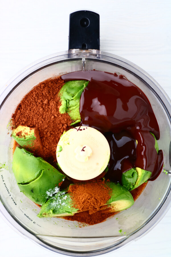 A food processor bowl filled with ingredients needed to make chocolate avocado mousse.