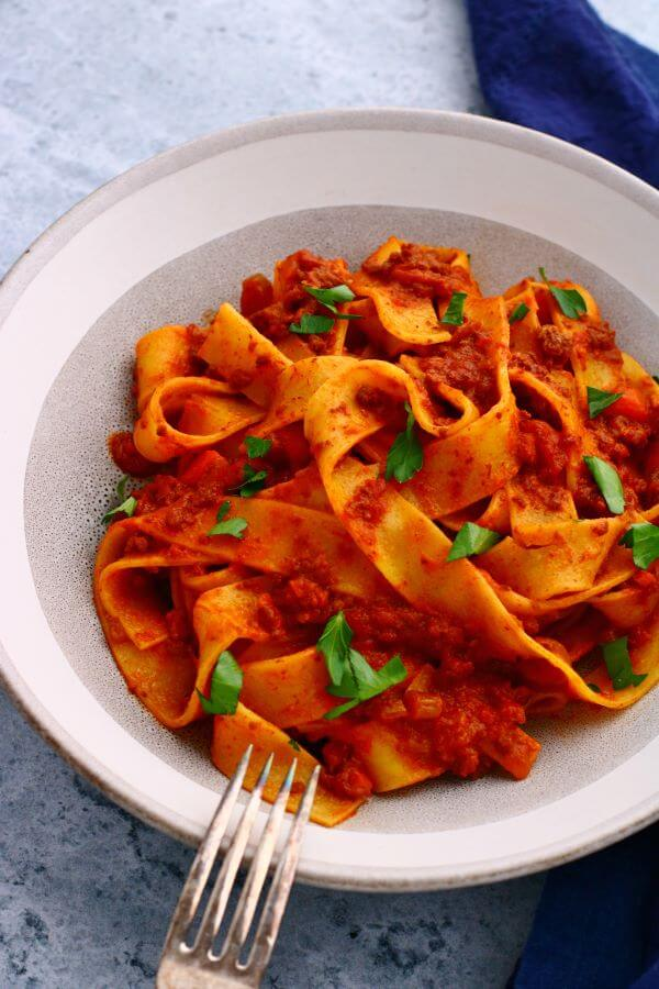 A bowl of wide flat papardelle noodles covered in bright red Bolognese.