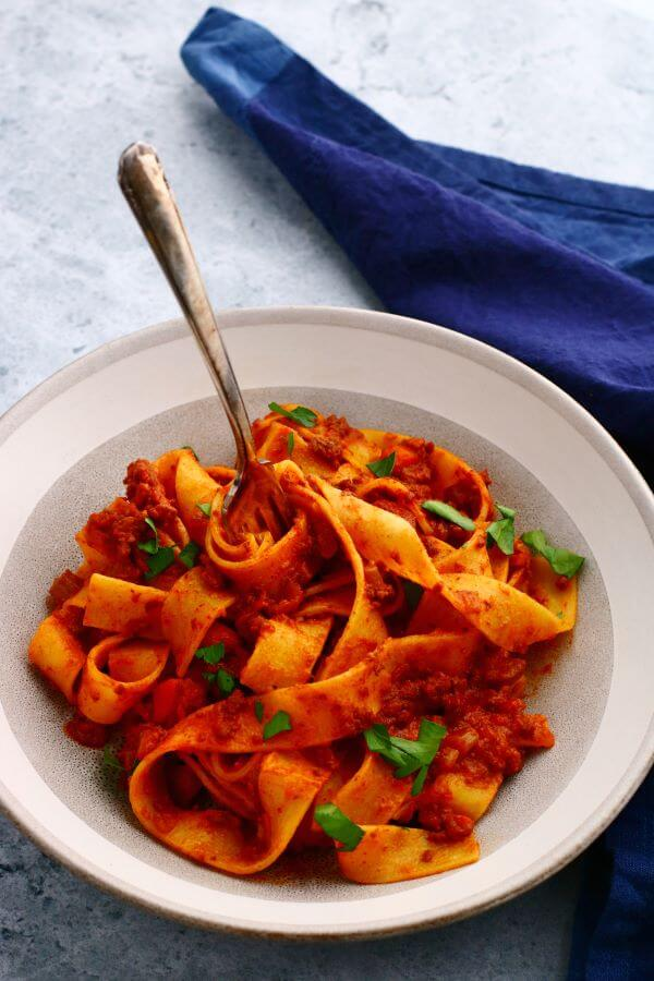 A fork standing in a bowl of wide flat papardelle noodles covered in bright red Bolognese.