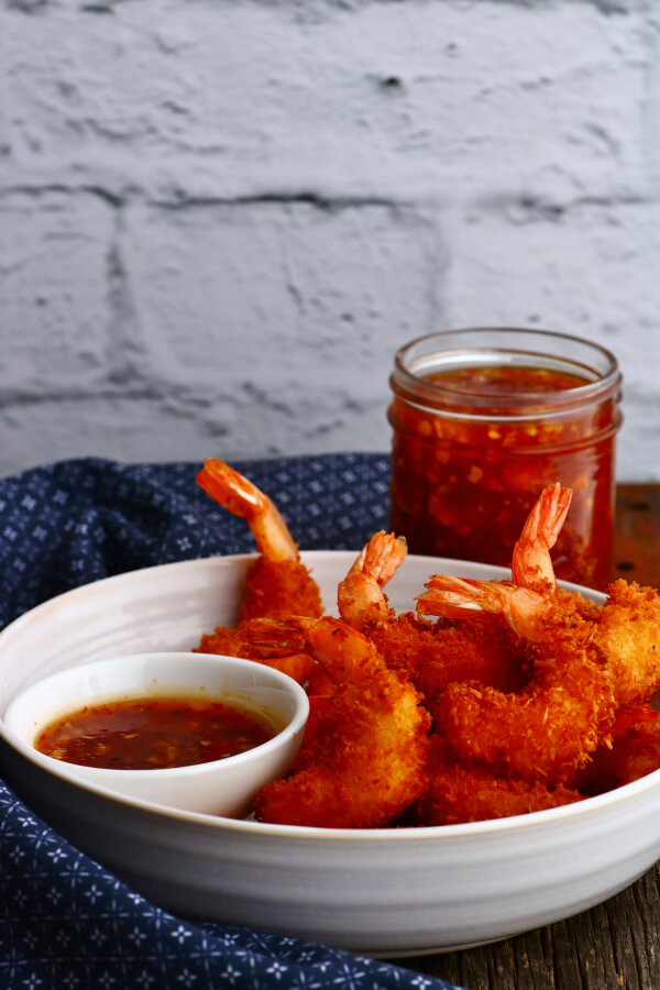 A bowl of crispy golden fried shrimp and red dipping sauce.