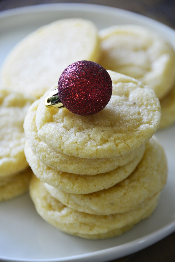 Eggnog Cookies stacked on a white plate with Christmas ball decorations.