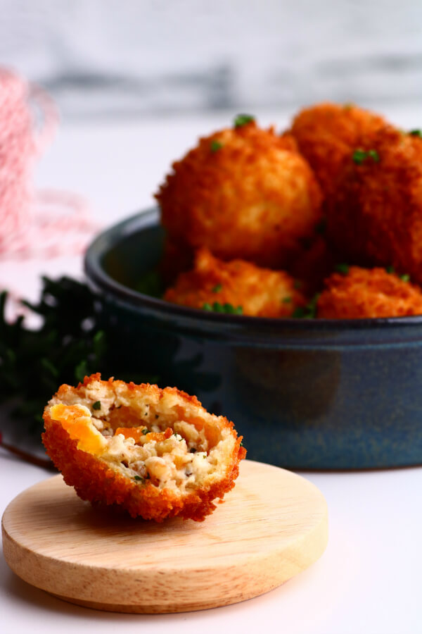 A blue bowl filled with golden fried goat cheese balls with one ball open to show gooey cheese.