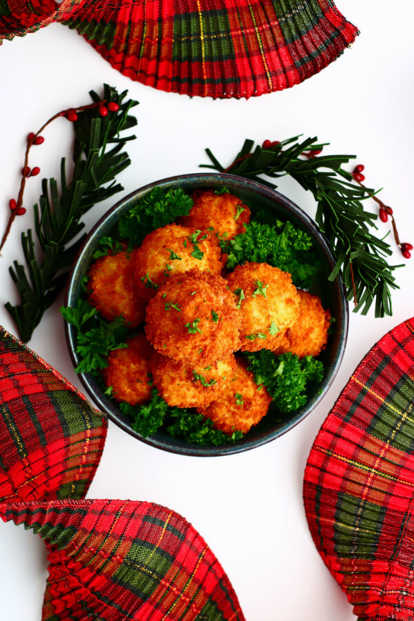 Overhead view of a blue bowl filled with golden fried goat cheese balls surrounded by plaid ribbons.