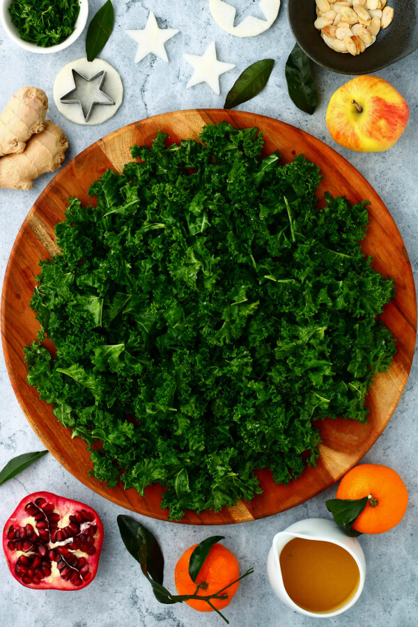 Massaged Kale on a wooden platter surrounded by salad ingredients.