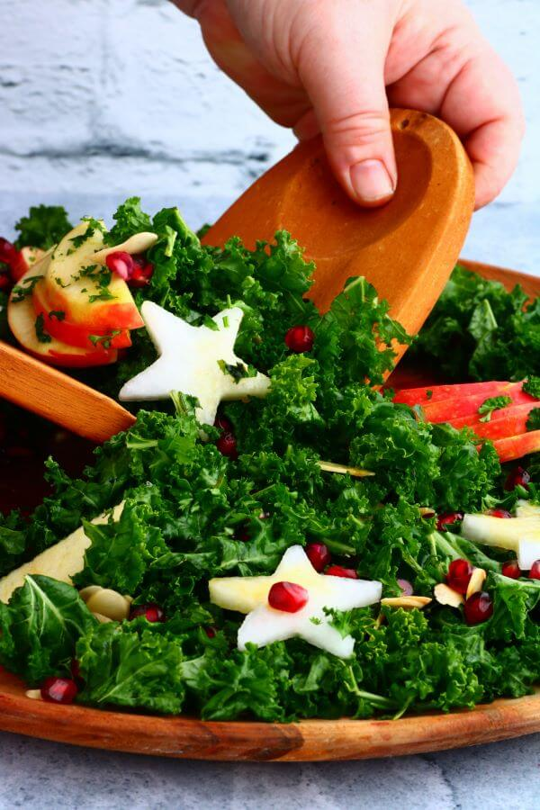 Wooden salad servers serving a leafy green massaged kale salad topped with apple slices, daikon stars, almonds, and pomegranate seeds.