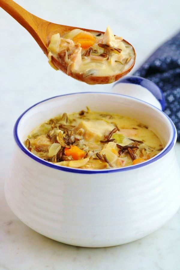 A spoon holds creamy chicken wild rice soup over a white bowl filled with the same soup.