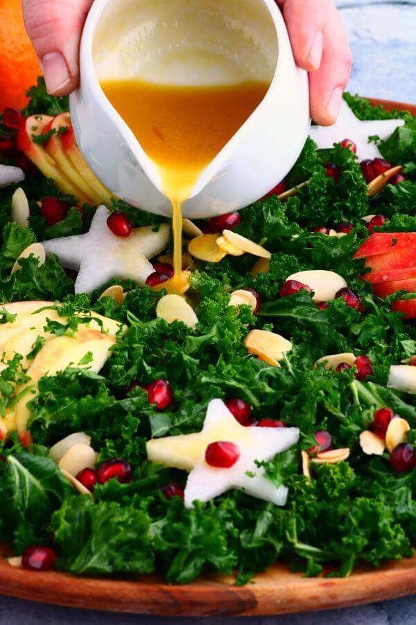 Mandarin orange vinaigrette being poured over a leafy green massaged kale salad topped with apple slices, daikon stars, almonds, and pomegranate seeds.