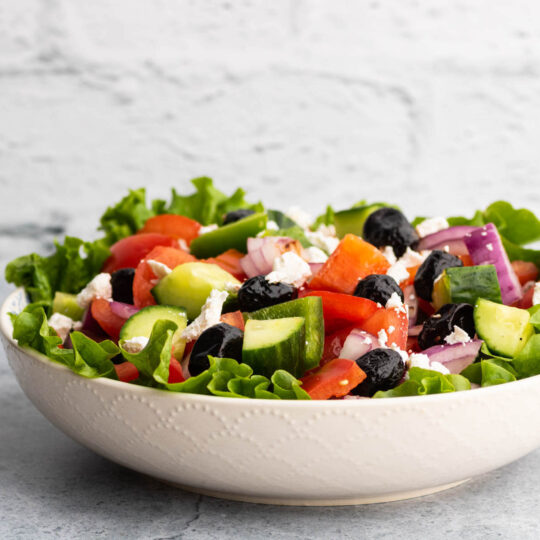 A white bowl filled with chopped tomatoes, peppers, red onions, cucumbers, black olives, and feta cheese.