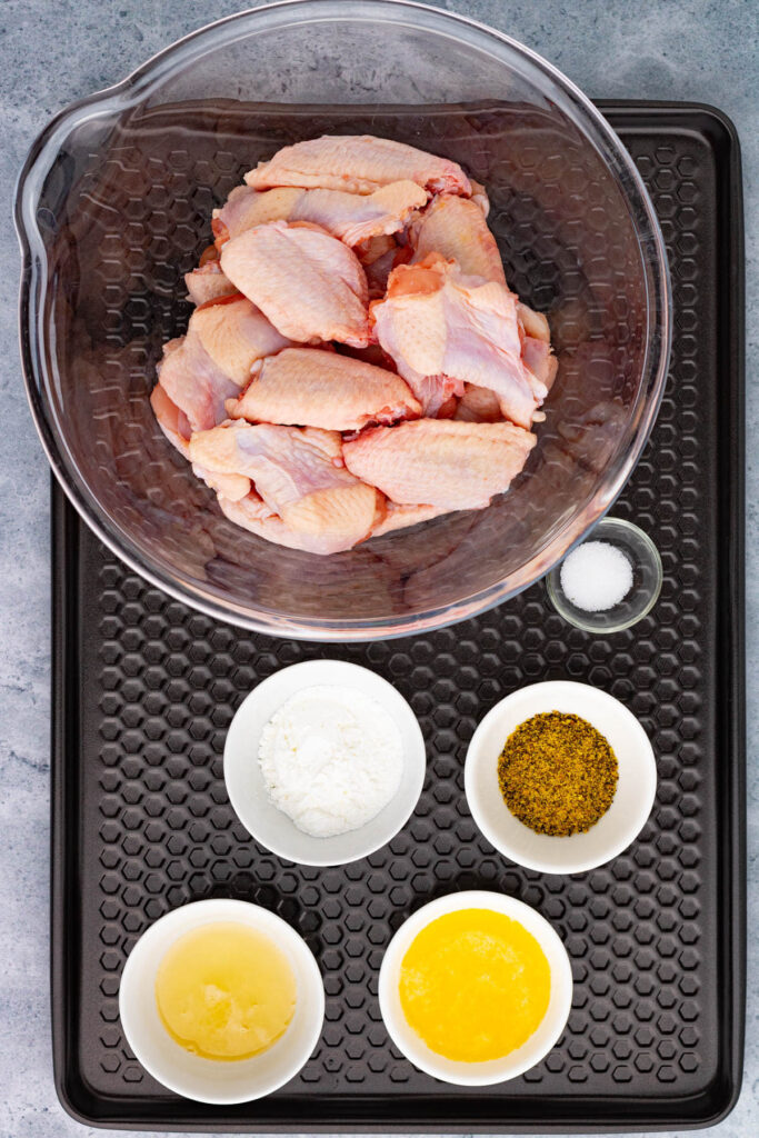 A baking tray containing the ingredients for baked Lemon Pepper Wings.