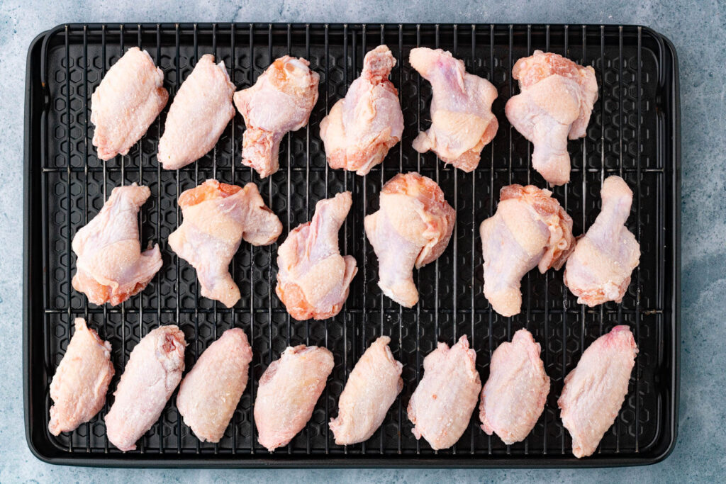 A baking sheet filled with raw chicken wings lightly coated in baking powder.