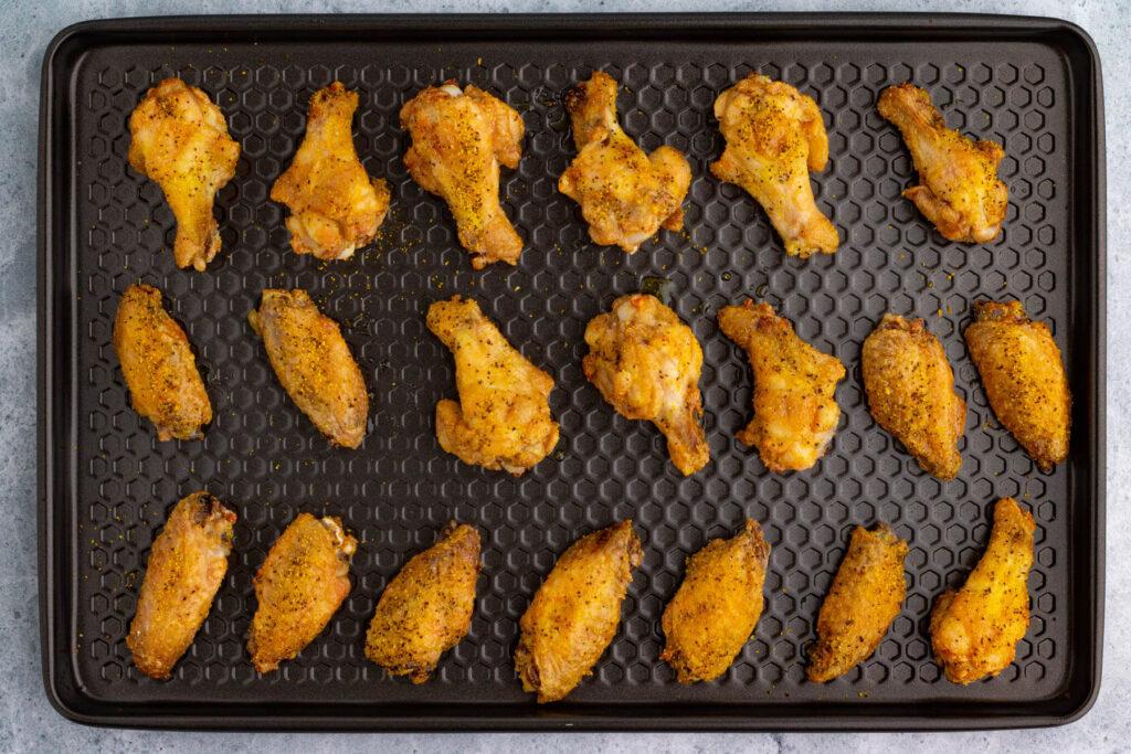 A baking sheet filled with crispy baked lemon pepper wings.