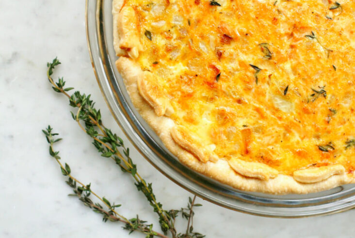 A golden baked quiche on white marble surrounded by fresh thyme.