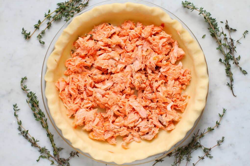 An unbaked pie shell filled with pink canned fish.