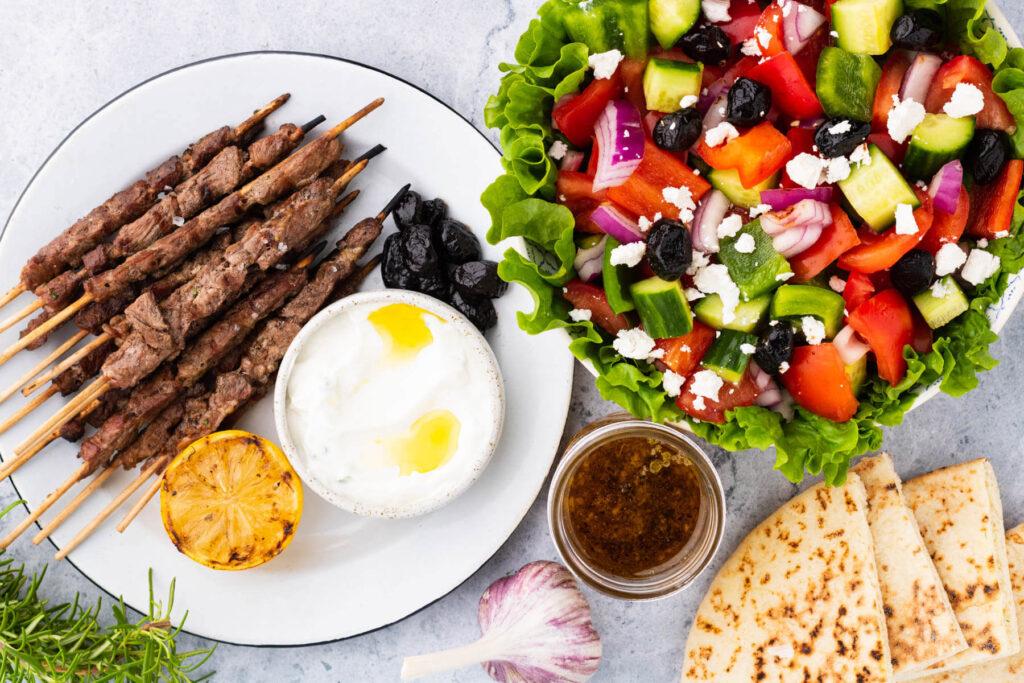 A Greek meal of Horiatiki Salad, Lamb Spiedini, Tzatziki, olives, and pita bread.