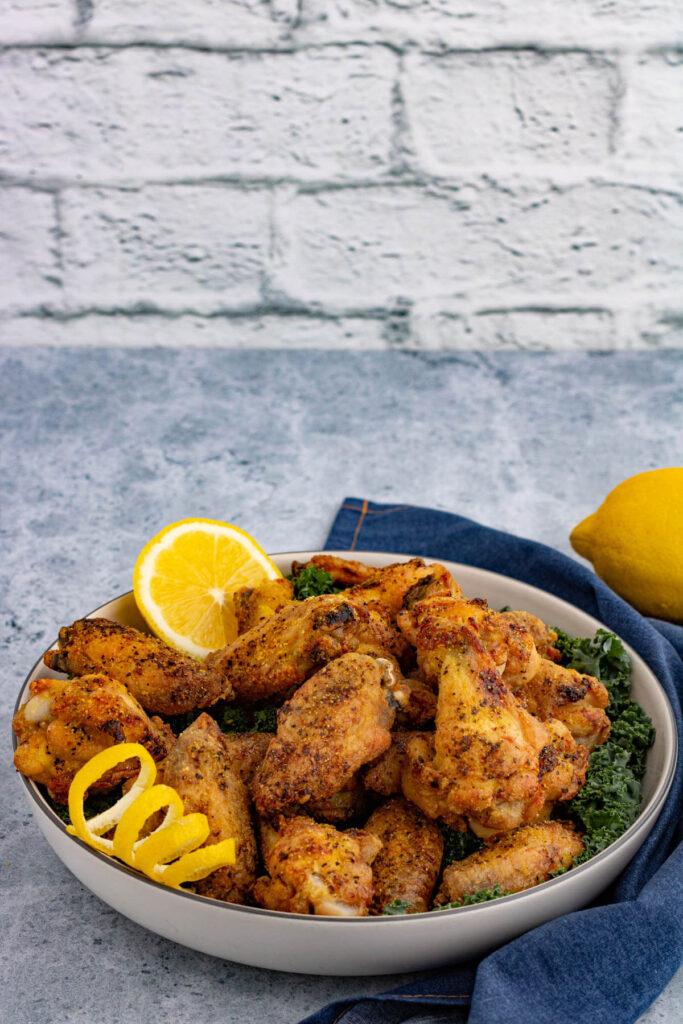 A bowl filled with golden baked lemon pepper wings, lemon peel curls and a slice of lemon.