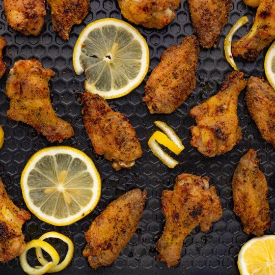 A baking sheet filled with crispy baked lemon pepper wings and lemon slices.