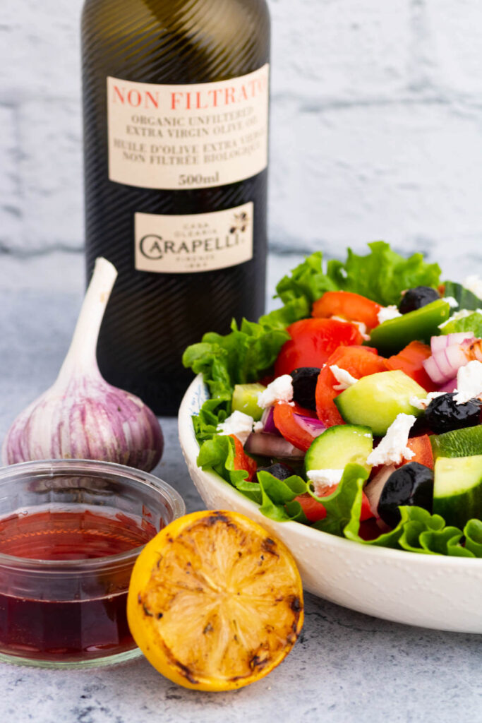 A white bowl of Horiatiki Salad of chopped vegetables, olives, and feta cheese beside vinaigrette ingredients.
