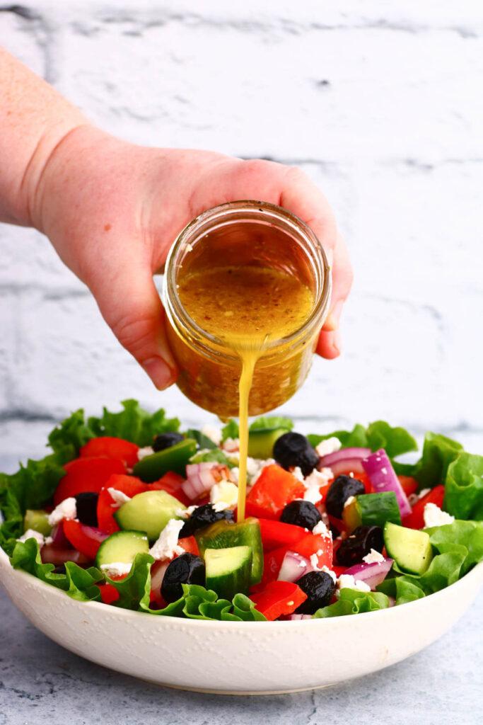 Golden dressing being poured over a chopped Horiatiki Salad, or Greek Village Salad.