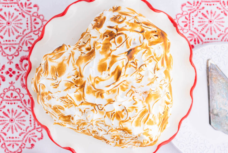 A heart shaped Baked Alaska covered in caramelized meringue on a red rimmed plate.