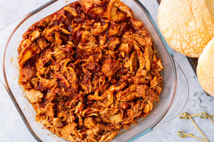 A glass baking dish containing BBQ Pulled Chicken beside buns.