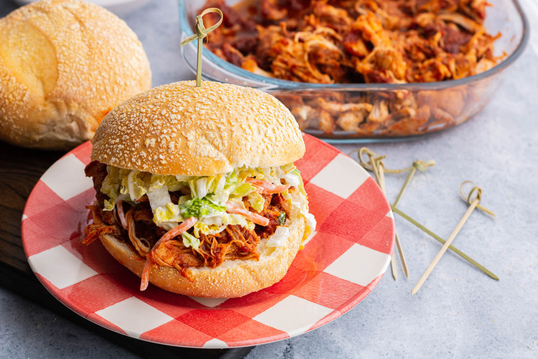 A soft white bun containing BBQ Pulled Chicken and coleslaw.