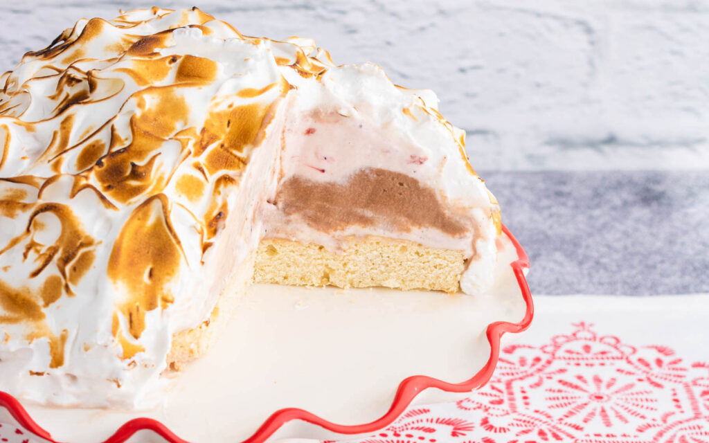 A heart shaped Baked Alaska with a slice taken out showing layers of ice cream.