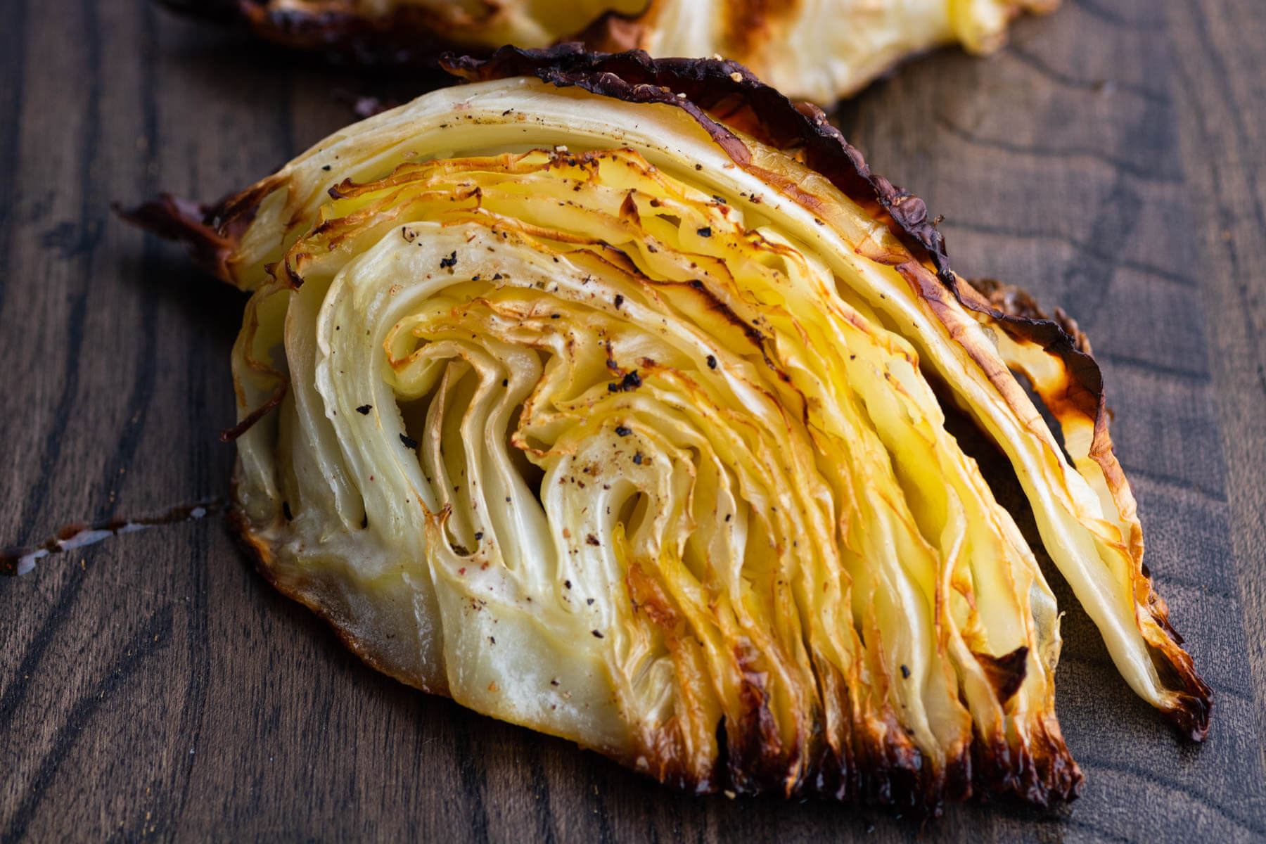 A wedge of Roasted Cabbage on a dark board.