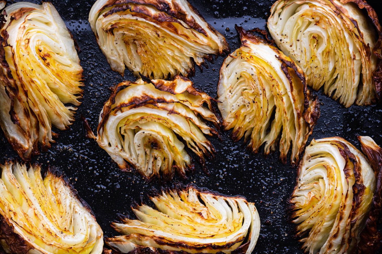 Roasted Cabbage Wedges in a dark roasting pan.