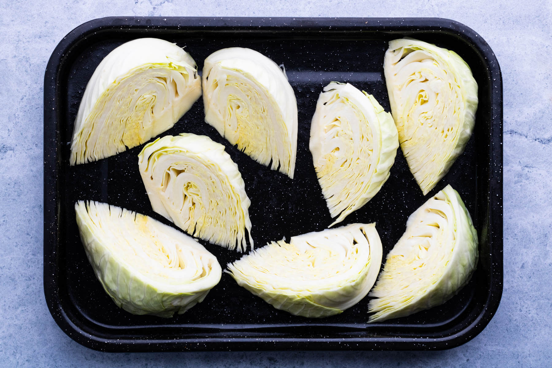 Wedges of raw cabbage in a dark roasting pan.