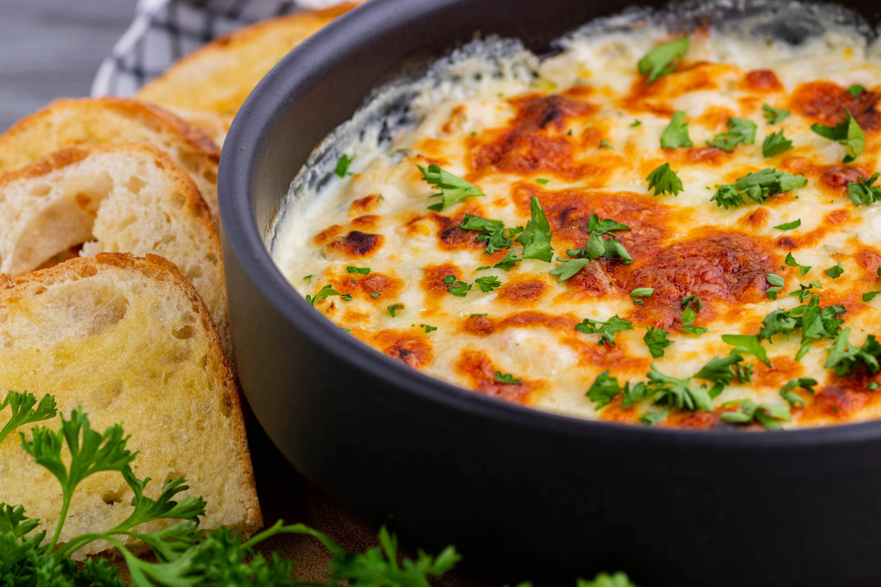 Close up of hot golden baked cheese dip with sliced baguette.