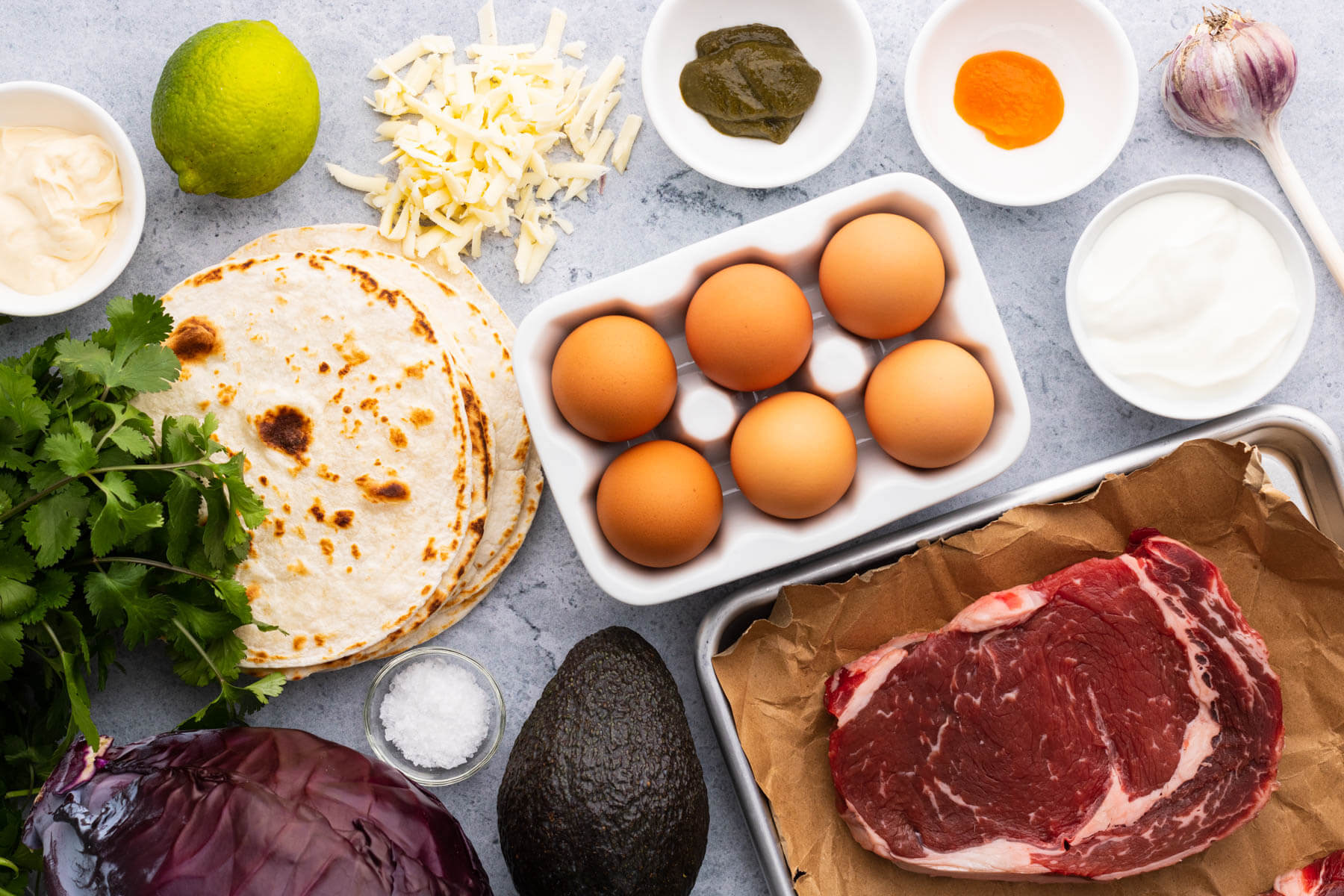 Ingredients photo featuring brown eggs, raw ribeye steak, avocado, cilantro, red cabbage, grated cheese, lime, and sauces.