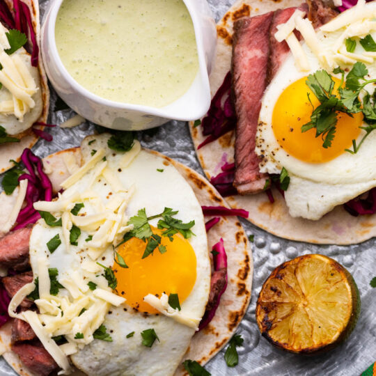 Three steak and egg tacos topped with cheese and cilantro.
