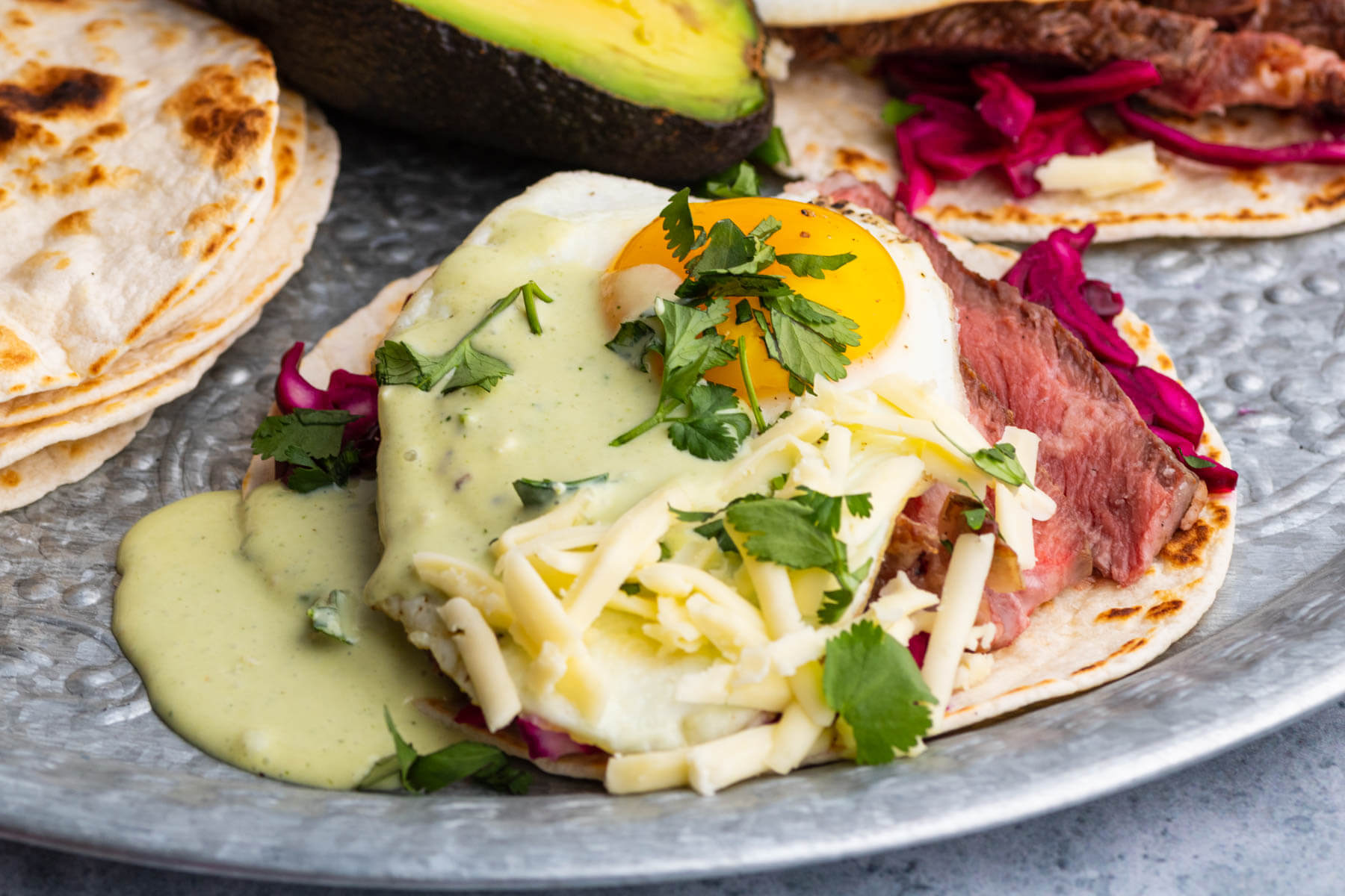 A steak taco topped with sunny side up fried egg, grated cheese, cilantro, and green sauce.