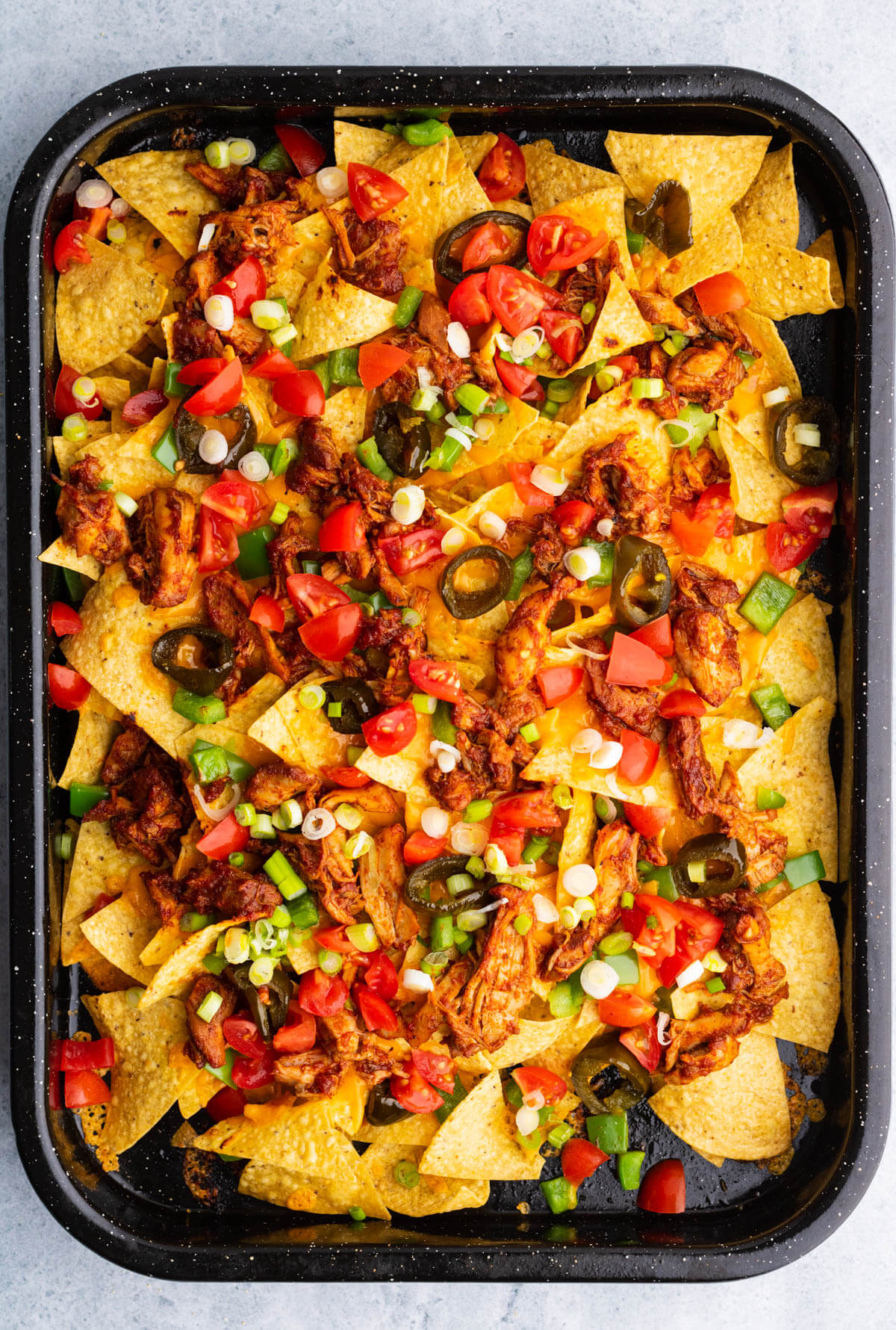 A tray of BBQ Chicken nachos with bright red tomatoes, green onions, and candied jalapenos.