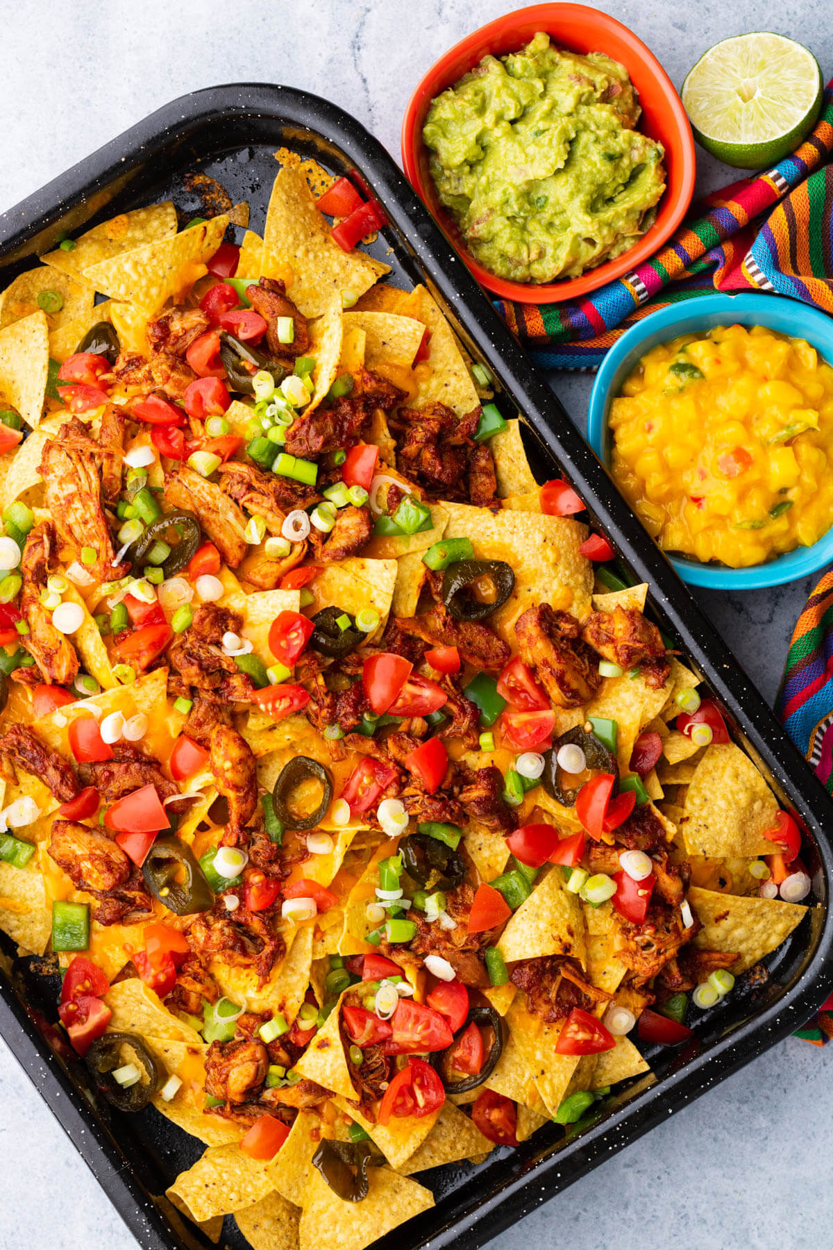 A colourful tray of BBQ Chicken nachos with two small side dishes of mango salsa and guacamole.
