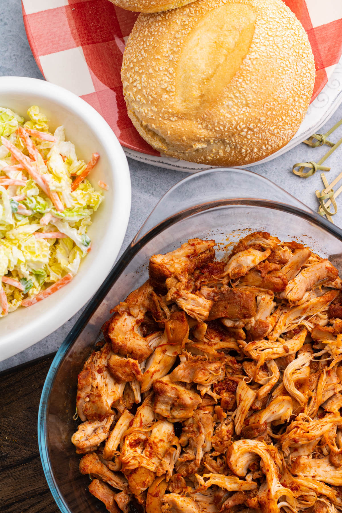 A glass baking dish containing BBQ Pulled Chicken a bowl of coleslaw and a white bun.