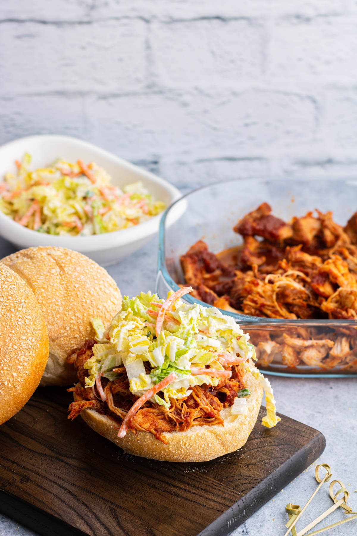 A soft white bun containing BBQ Pulled Chicken and coleslaw surrounded by a glass dish of BBQ Pulled Chicken, coleslaw, and buns.