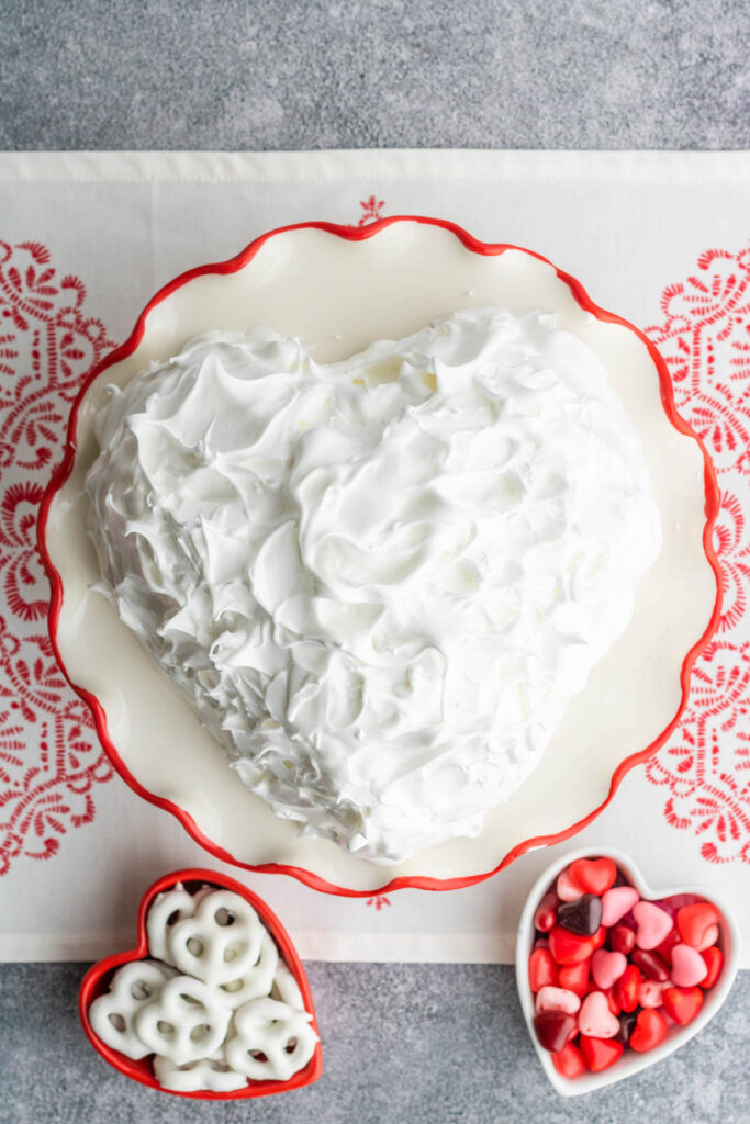 A heart shaped Baked Alaska covered in white meringue on a red rimmed plate.