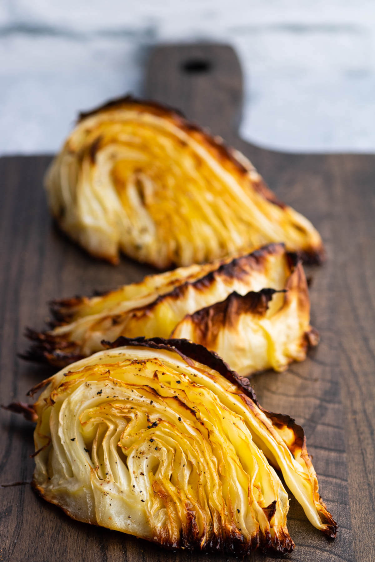 Wedges of Roasted Cabbage on a dark board.