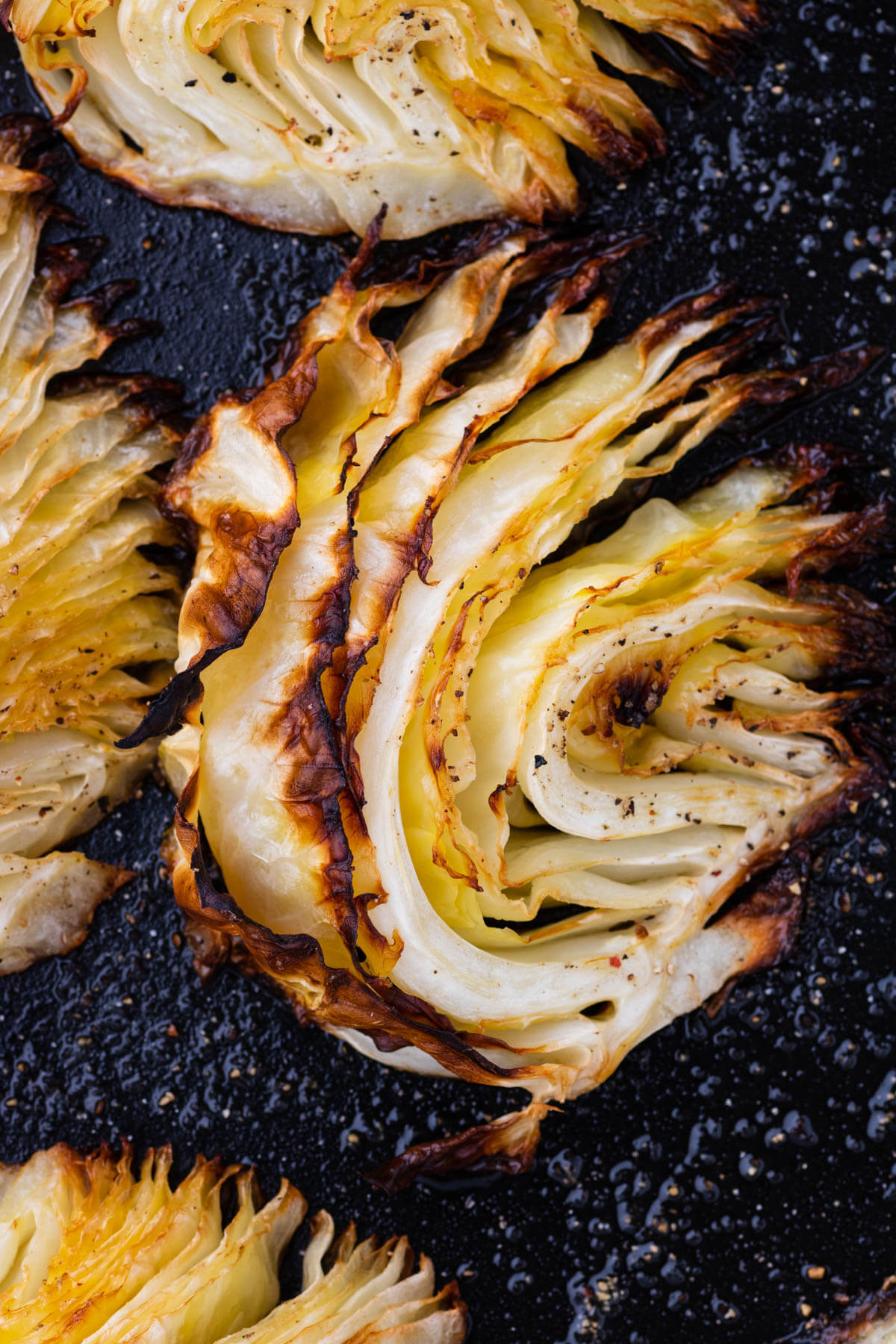 A wedge of Roasted Cabbage in a dark roasting pan.