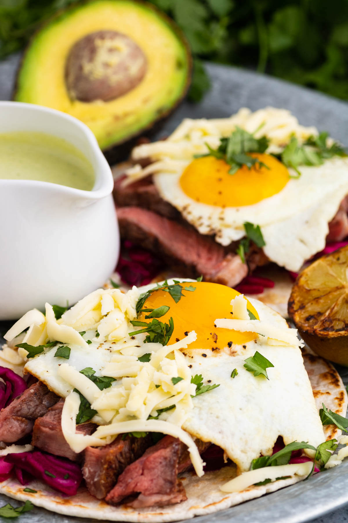 Close image of a steak taco topped with sunnyside up fried egg garnished with cheese and cilantro.