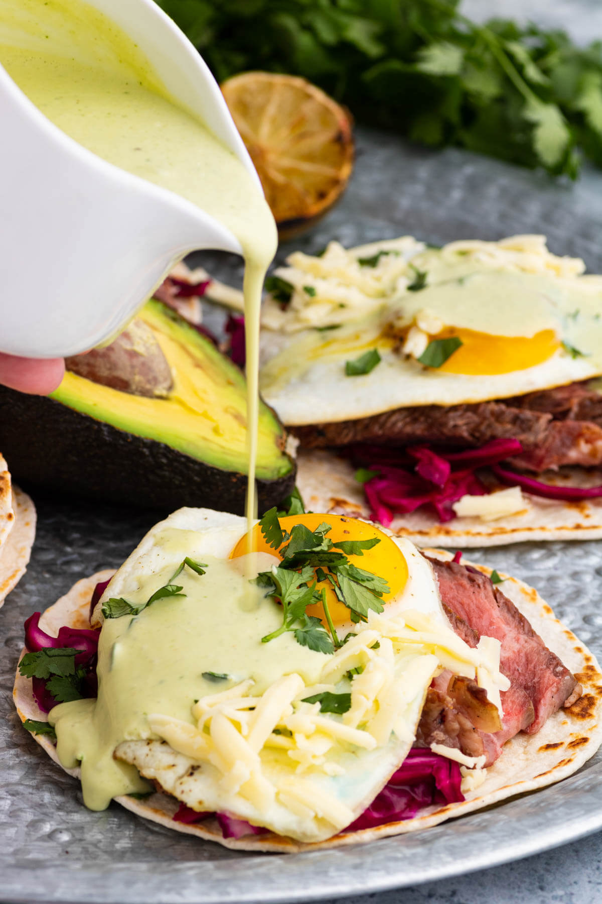 Green sauce being poured over a steak and egg taco.