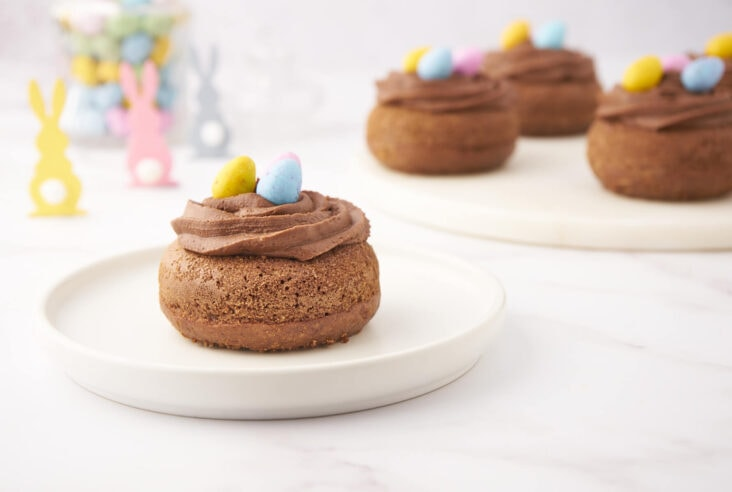 Chocolate baked donuts decorated as Easter Nests filled with Mini Eggs in an Easter table setting.
