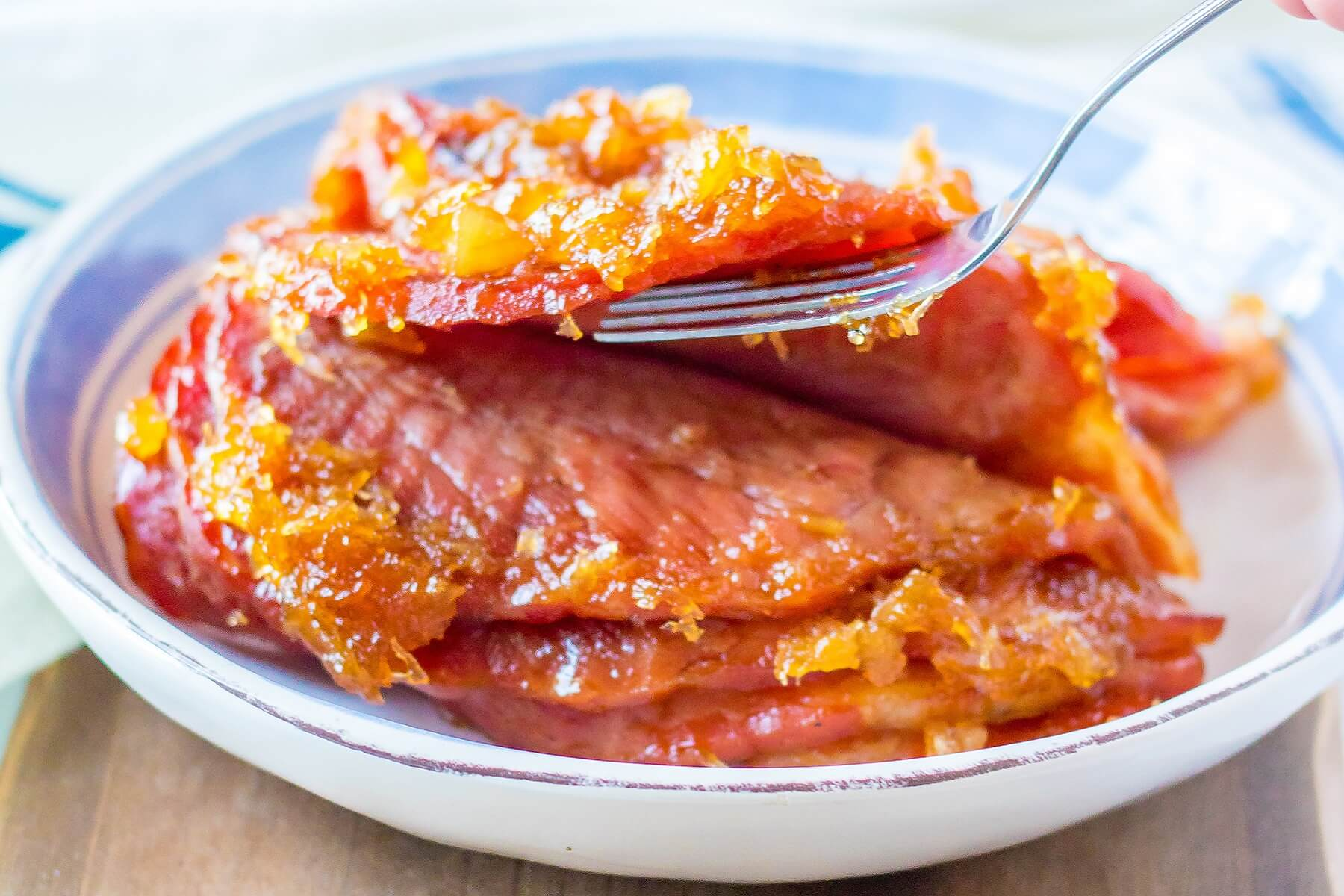 A fork takes a slice of ham coated in pineapple cola glaze.