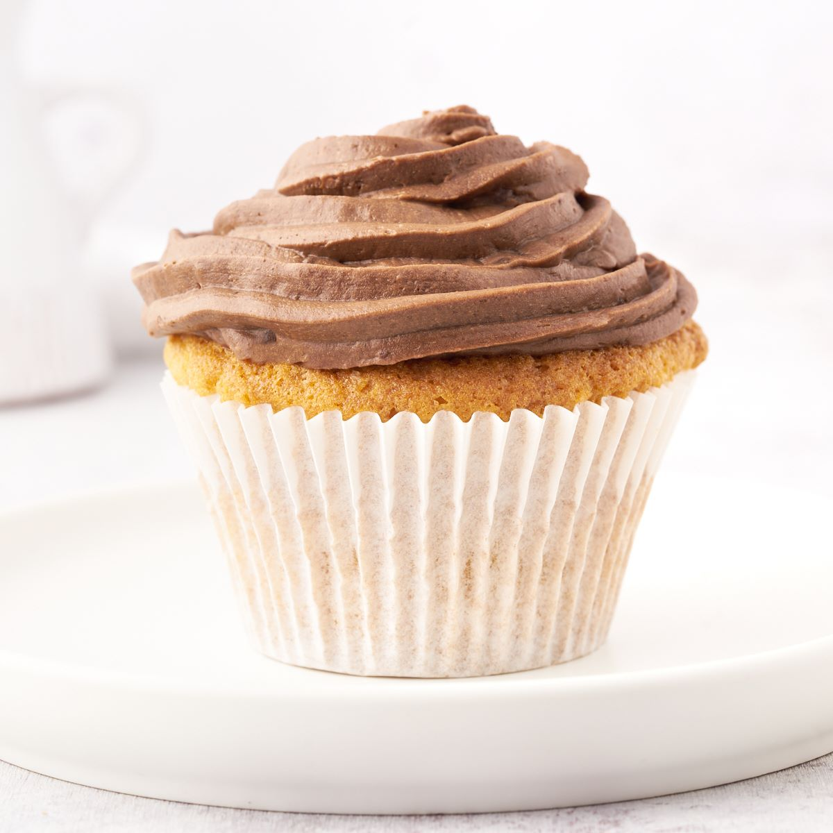 A vanilla cupcake frosted with swirled Nutella frosting.